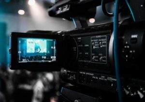Behind a video camera where a small screen records a video of someone being interviewed
