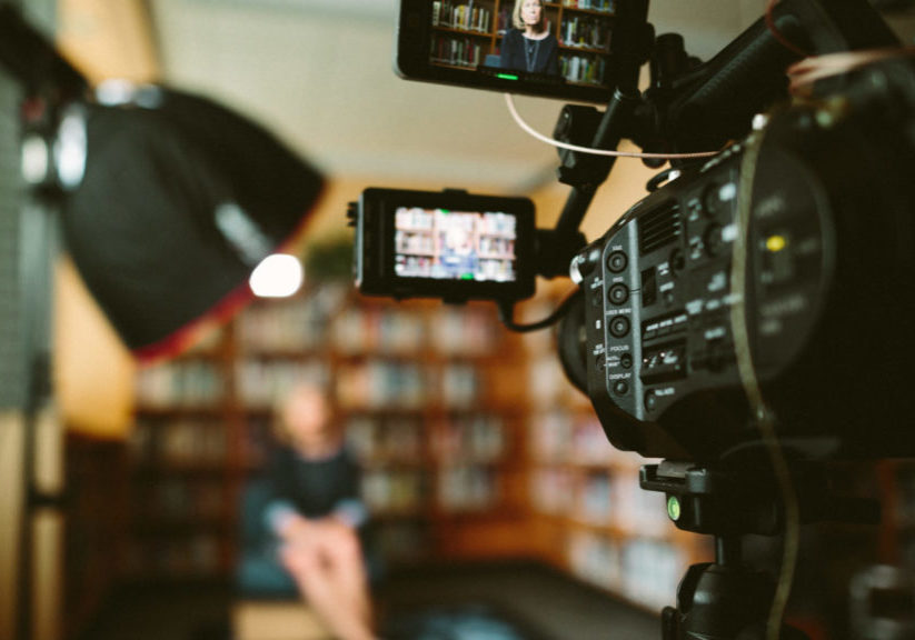 A photo of a person being recorded for an interview on-camera