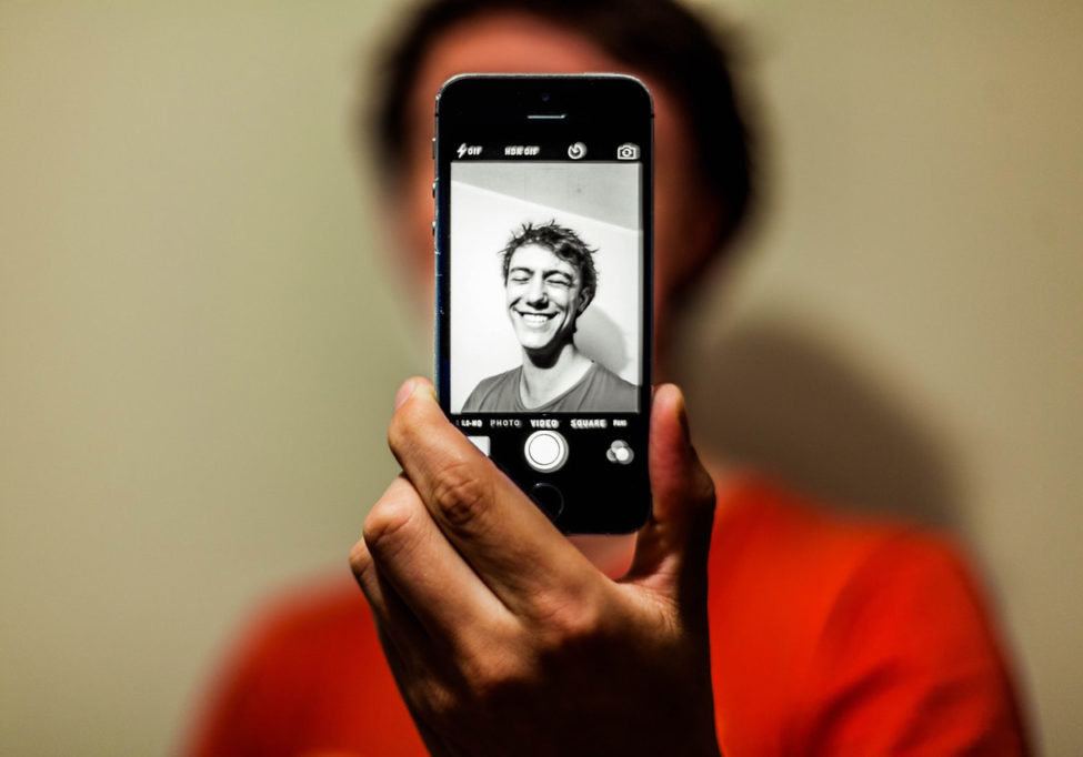 How to take a good selfie video - Man in Red Shirt Having Selfie on His Iphone in Grayscale Mode